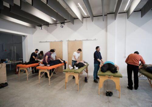 Imagine din timpul unui atelier de masaj de La Firul Ierbii. Mai multe mese sunt înșirate, iar participanții exersează diferite tehnici de masaj.