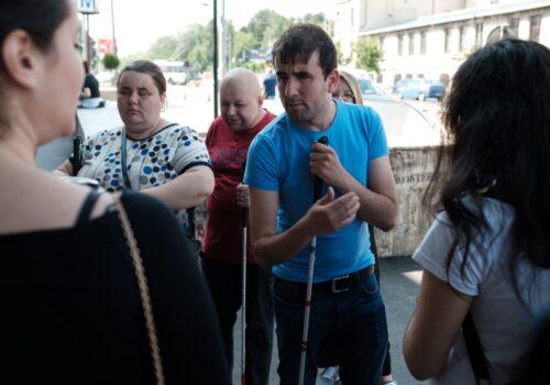 Participanții de la un exercițiu de mobilitate așteaptă în fața gurii de metrou.