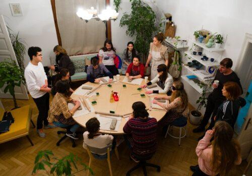 Participanți în jurul mesei lucrează la decorul farfuriilor din cadrul unui atelier de ceramică