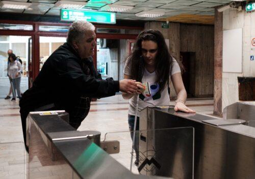 O persoană nevăzătoare este ajutată de paznic să treacă de turnicheții de la metrou.