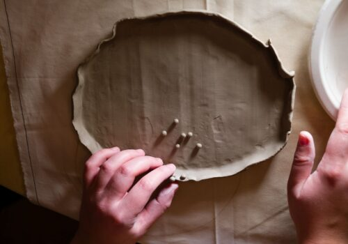Prim plan cu mâinile unui participant și obiectul de ceramică creat de acesta.