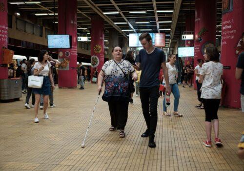 Un participant și un voluntar se deplasează pe peronul de la metrou.