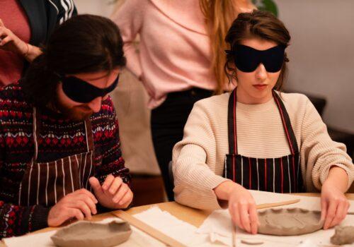 2 participanți tipici cu ochelari opaci modelează obiecte de ceramică.