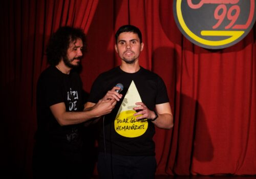 """Mihai Grecu ține microfonul în mână în cadrul unui show de stand-up. Pe tricoul lui scrie """"Doar glume nemaivăzute""""."""
