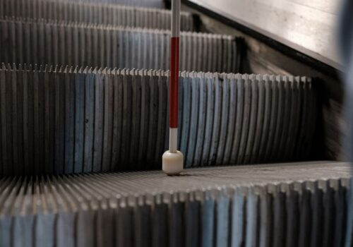 Prim plan cu vârful unui baston sprijinit de o treaptă a unor scări rulante de la metrou.