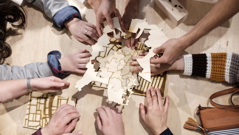 Mai multe mâini care completează harta tactilă a Bucureștiului.