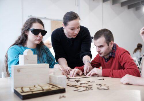 Un nevăzător și o persoană tipică cu ochelari opaci explorează împreună o hartă tactilă, în timp ce un voluntar le dă indicații verbale