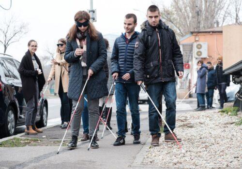 2 nevăzători și o persoană tipică cu ochelari opaci se deplasează folosindu-se de baston în afara spațiului de La Firul Ierbii.