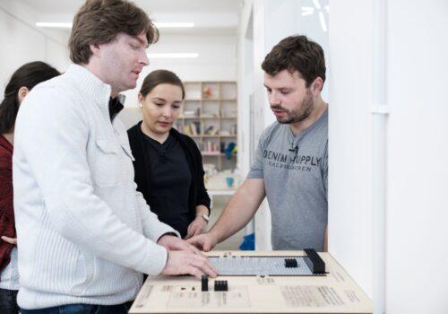 Mai multe persoane explorează harta tactilă cu sala multifuncțională de La Firul Ierbii. Aceasta este compusă din piese lego și este modificată în funcție de schimbările din sală.