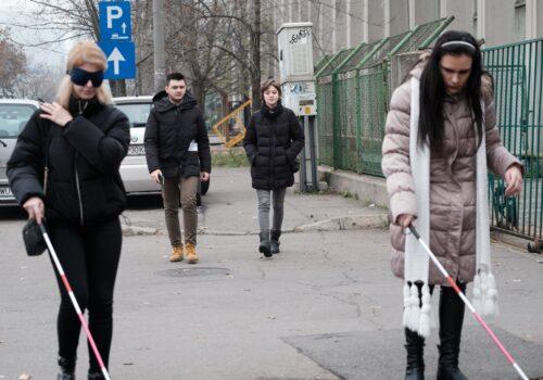 O persoană nevăzătoare și o persoană tipică cu ochelari opaci se deplasează pe Splaiul Unirii folosindu-se de bastoane. În spatele lor se află doi trecători, care se uită spre ei.