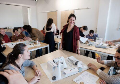 Mai multe mese cu participanți care construiesc machete din hârtie. Printre mese se plimbă voluntari: unii zâmbesc, iar alții sunt aplecați peste machete și vorbesc cu participanții.