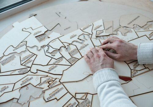 Imagine cu mâinile unei persoane care explorează o hartă tactilă cu principalele zone din București.
