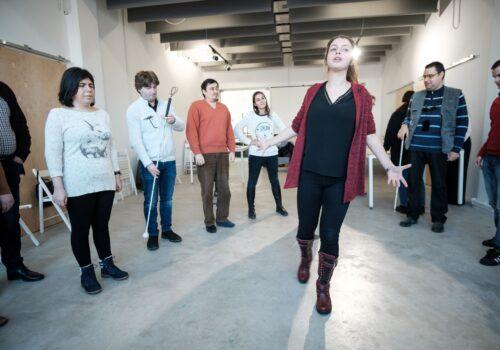 Imagine din timpul unui atelier de dezvoltare personală: mai mulți participanți sunt adunați în cerc, iar trainerul se află în mijlocul lor vorbind și gesticulând.