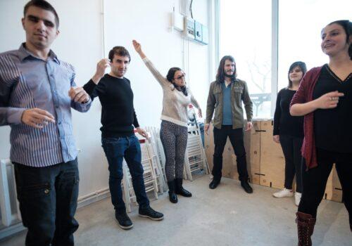 Imagine din timpul unui atelier de dezvoltare personală: participanții se află în cerc și fac diferite gesturi victorioase.