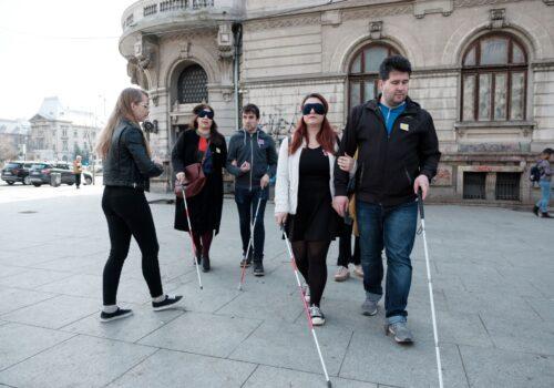 2 perechi de persoane se îndreaptă folosindu-se de baston spre facultatea de arhitectură. Între cele două echipe se află un voluntar uitându-se spre ei atent.