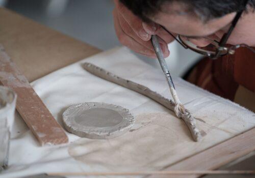 Imagine din timpul unui atelier de ceramică: aceasta este focalizată mâna unui participant care își umezește obiectul de ceramică cu ajutorul unei pensule.