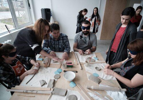 Masa unor participanți din timpul atelierului de ceramică: aceasta este plină cu instrumente și bucăți de gresie, iar participanții lucrează de zor, asistați de voluntari.