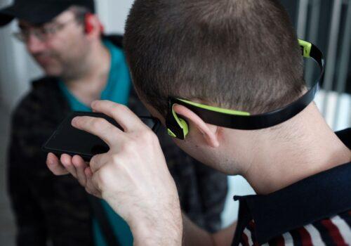Imagine focalizată pe căștile cu conducție osoasă ale unui participant. Acesta umblă pe telefon în timp ce ascultă indicațiile la căști.
