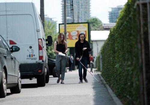 Un participant se plimbă pe stradă folosindu-se de baston și asistat de un voluntar în timpul unui exercițiu de mobilitate.