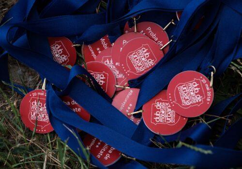 """Mai multe medalii adunate pe iarbă, care urmează să fie împărțite participanților la finalul probei de mobilitate de la finalul primei generații a Clubului de Mobilitate Urbană. Pe medalie se poate vedea scris """"20 mai 2018"""" și emblema clubului."""