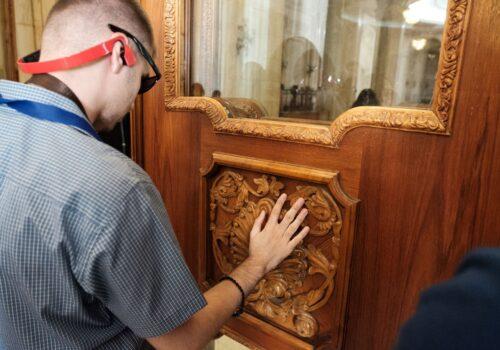 Un participant nevăzător explorează modelul complex al unei uși de lemn din cadrul unei săli din Palatul Parlamentului