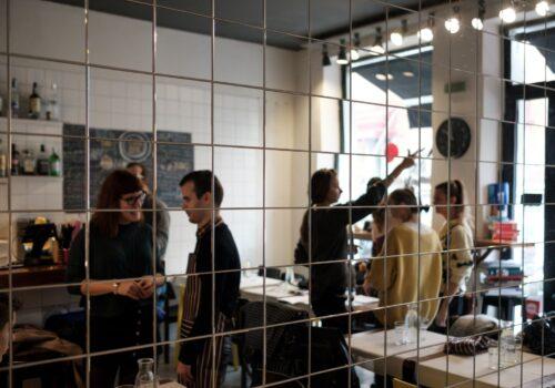 Imagine cu reflexia dintr-o oglindă a participanților de la un atelier de gătit.