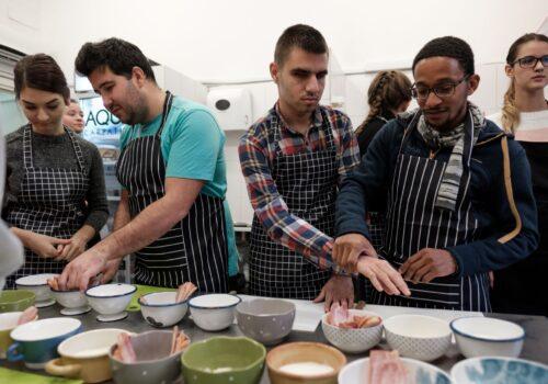 Participanții de la atelierul de gătit sunt înarmați cu șorțuri și cu voie bună. Aceștia explorează bolurile cu ingrediente din fața lor.