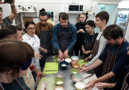 Trainerul de la atelierul de gătit le vorbește participanților care sunt strânși în jurul mesei cu ingrediente.