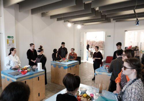 Participanții de la atelierul de gătit sunt împărțiți pe grupe și ascultă indicațiile trainerului.