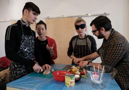Participanții gătesc o salată de iarnă, iar voluntarii stau lângă ei și le explică ceva.