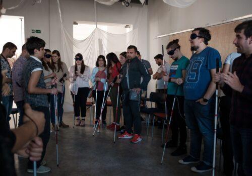 Participanții stau în cerc în sala de activități, fiecare cu un baston în mână.