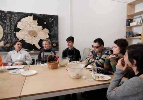 Participanții de la atelierul de gătit stau la masă și mănâncă împreună rezultatul muncii lor- o salată delicioasă de iarnă.