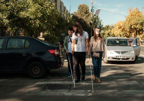 3 participanți traversează strada folosindu-se de baston pentru a repera obstacolele.