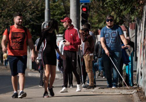 Interacțiune dintre un participant și oamenii de pe stradă: participantul înaintează cu bastonul, iar oamenii de pe stradă întorc capul după el.