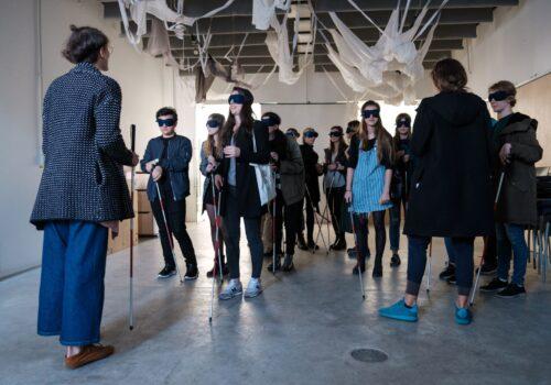 Participanți tipici cu ochelari opaci și cu bastoane ascultă indicațiile trainerului pentru un mic exercițiu de empatie.