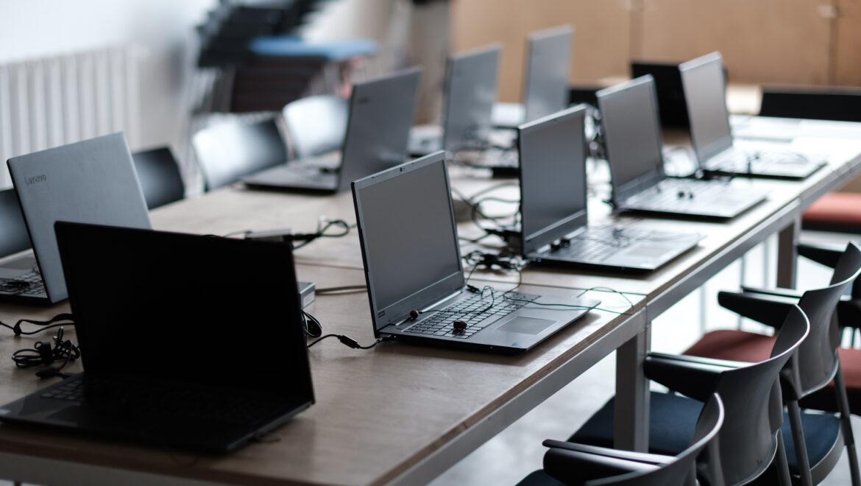 Sala pregătită pentru cursuri cu laptop-urile aranjate pentru participanți.