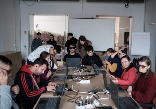 Participanții aranjați în jurul mesei de lucru, sunt îndrumați de traineri și voluntari în rezolvarea exercițiilor propuse pe laptop.