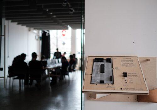 Imagine de perspectivă, în prim plan este harta lego unde este reprezentată tactil sala de activități, iar în fundal se află participanții așezați la mese