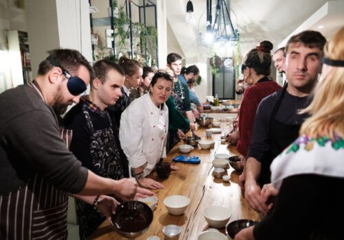 De-a lungul unei mese plină cu ingrediente pentru desertul ce urmează a fi preparat, participanții lucrează cu instrumentele de bucătărie
