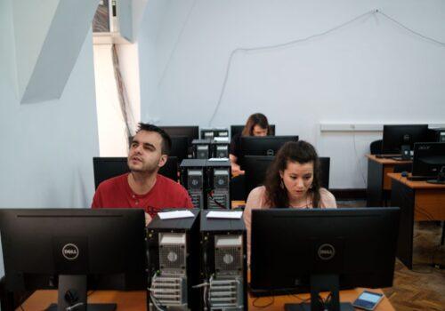 Două persoane stau în fața unui calculator și îl operează în cadrul hub-ului de programare
