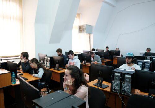 Participanții hub-ului de programare stau în băncile unei săli din cadrul Facultății de Matematică și Informatică și lucrează pe PC.