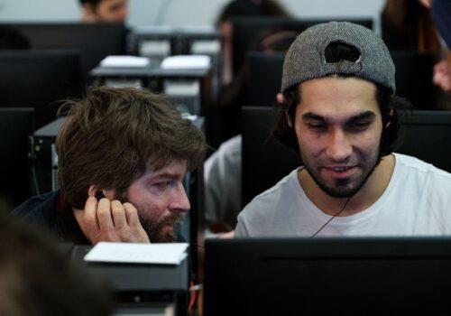 Doi participanți lucrează împreună pe PC, ascultând fiecare la câte o cască ceva.