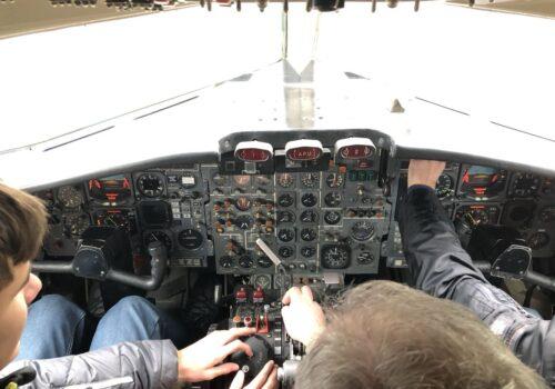 Doi participanți se află la bordul unui avion și explorează butoanele panoului de comandă.