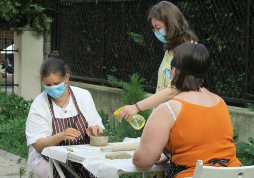 2 participanți modelează obiecte de ceramică, iar un voluntar îi ajută să-și umezească gresia