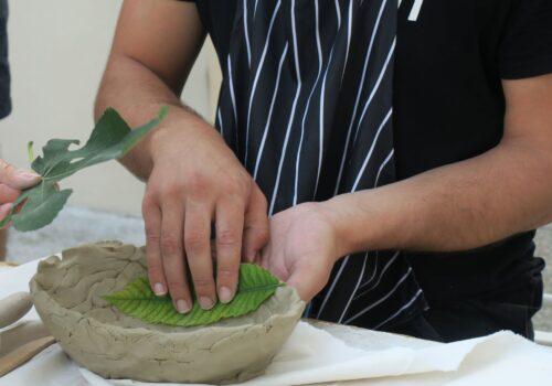 Un participant își imprimă obiectul de ceramică cu texturi vegetale.