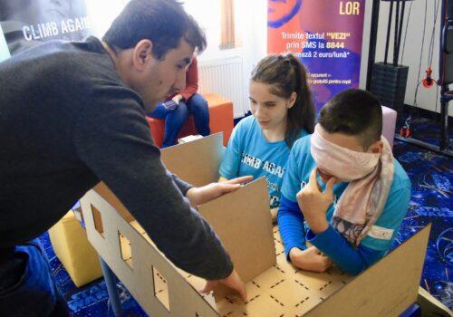În cadrul atelierului cu machete, doi elevi de la Școala Austrului construiesc casa lor de vis, alături de voluntar.