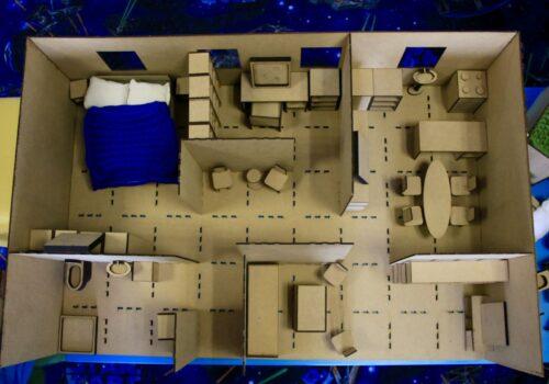 Imagine de sus cu macheta construită de elevi: aceasta ilustrează o casă cu mai multe încăperi mobilate.