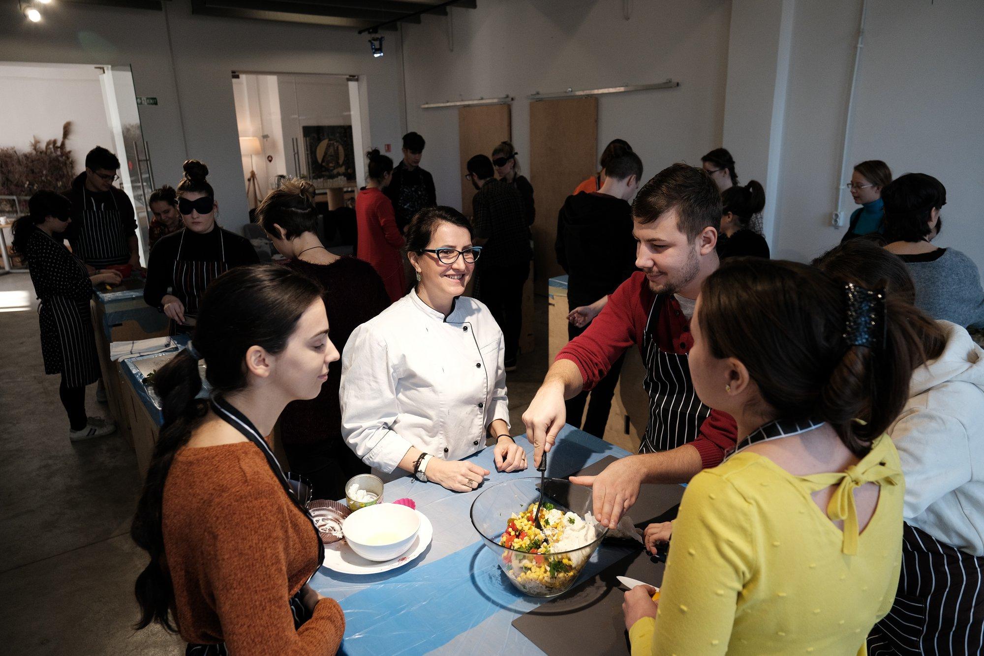 Exploratori în jurul meselor la atelierul de gătit