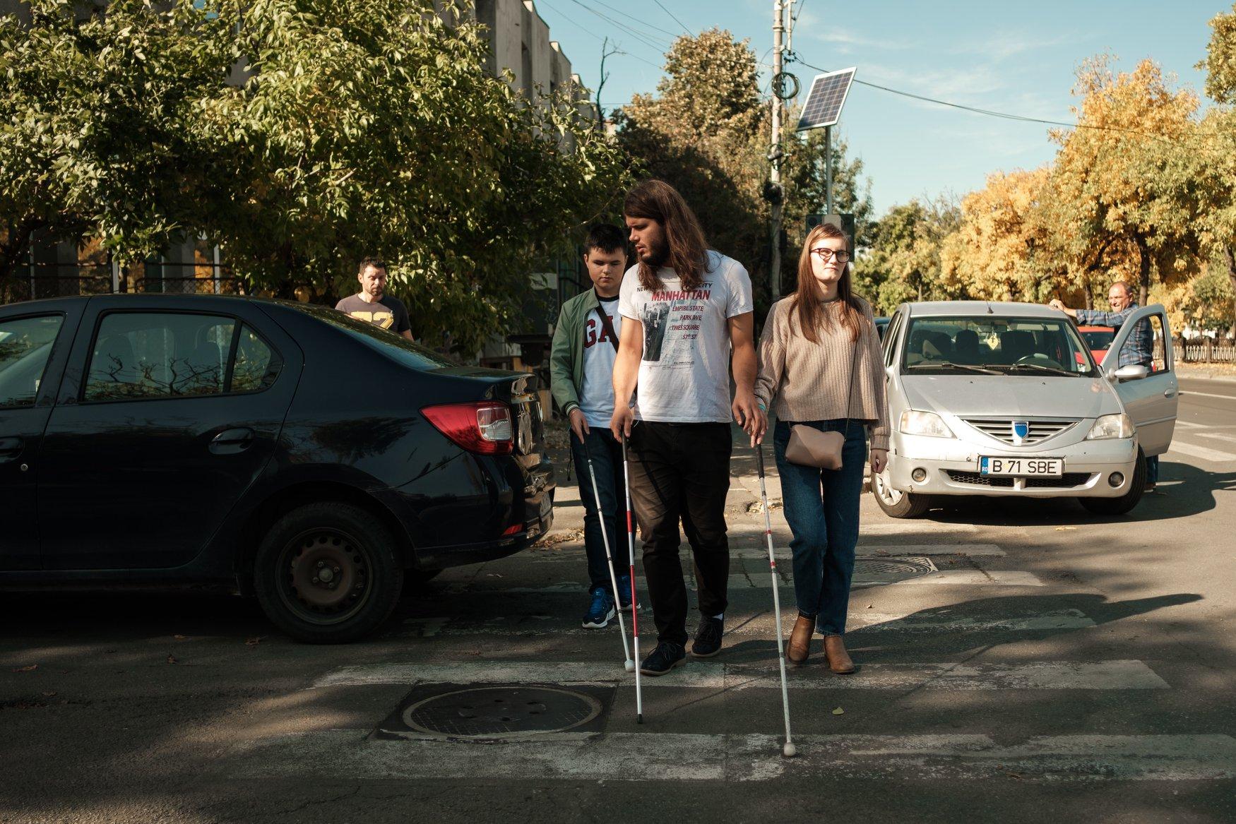 Exploratori cu bastone trec strada pe trecerea de pietoni, printre mașini parcate.