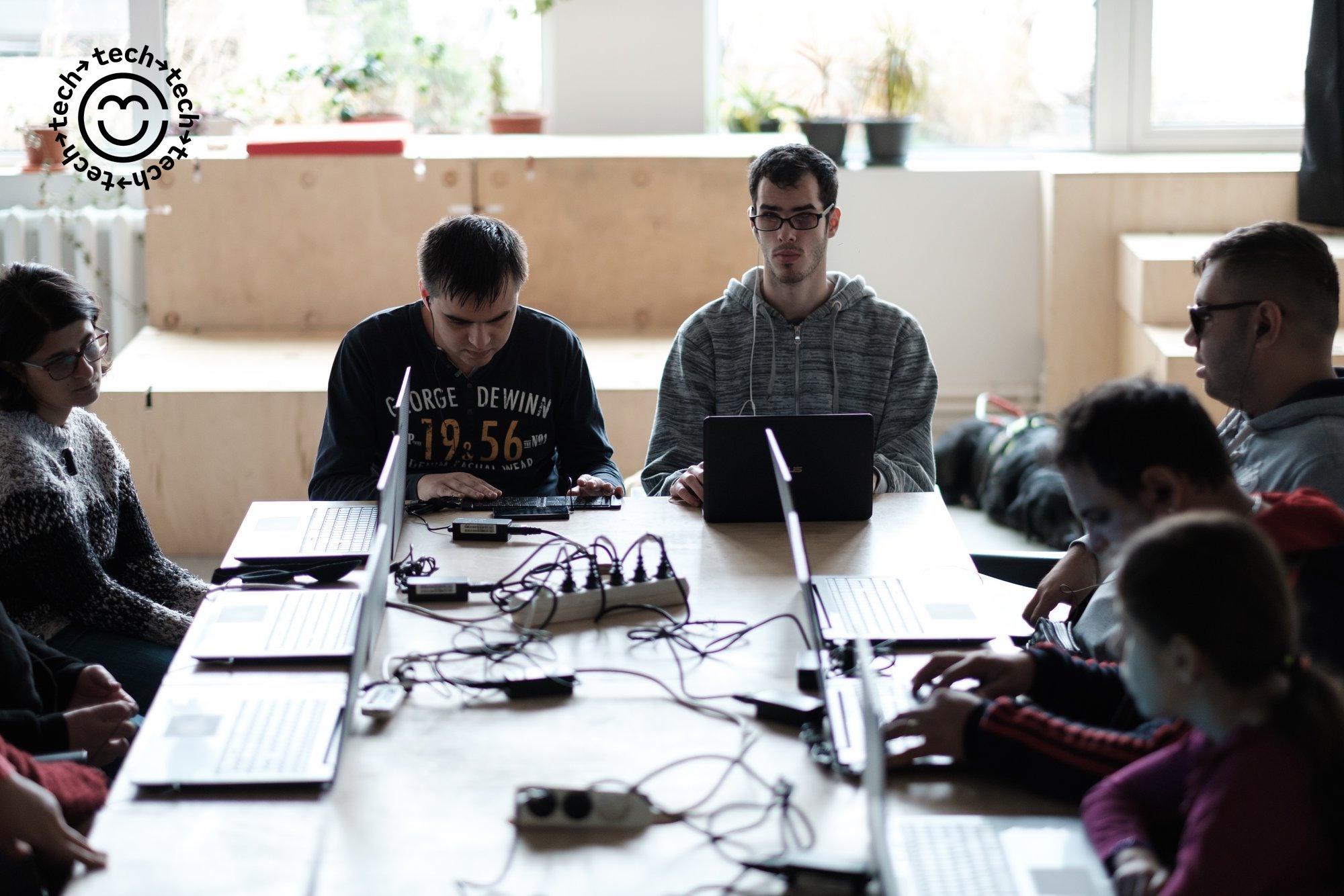 Exploratori cu laptopuri la atelierul de tehnologie asistivă